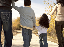 Backview of a family of four holding hands and walking in the park